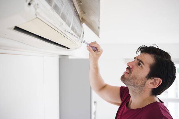 Mann med en skrutrekker som står å fikler med et air-condition-anlegg på en vegg