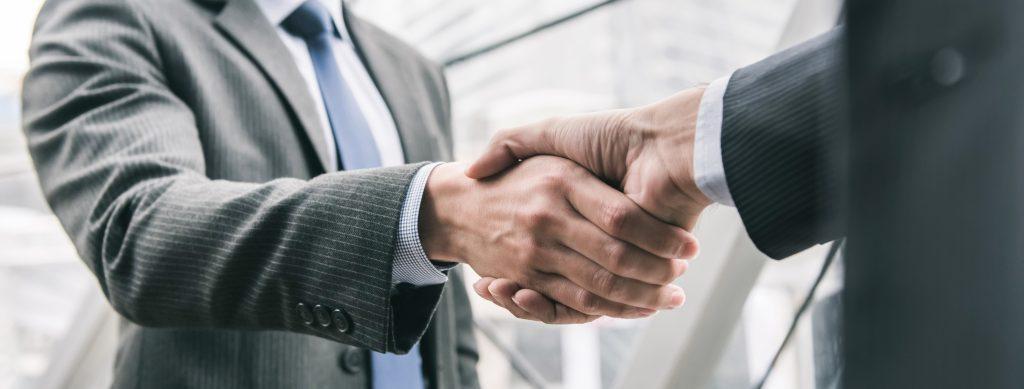 To forretningsmenn som tar hverandre i hånden som representasjon for gjennomført salg av rørlegger-firma